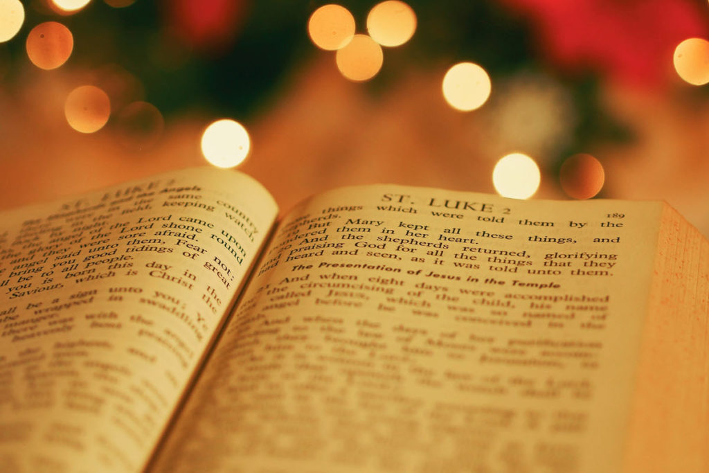Bible open to Luke with Christmas lights in the background