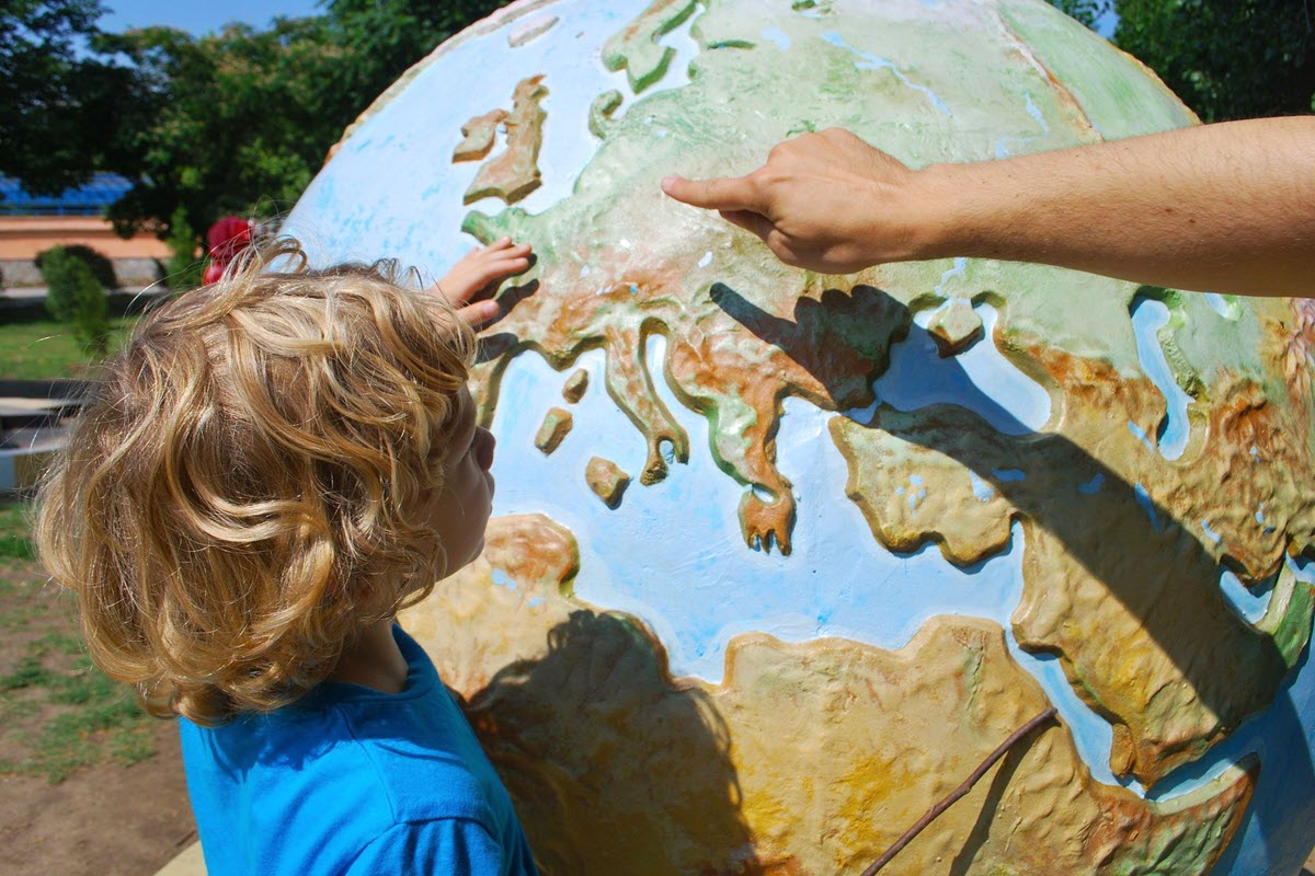Child looking at a large globe of earth while adult points at europe