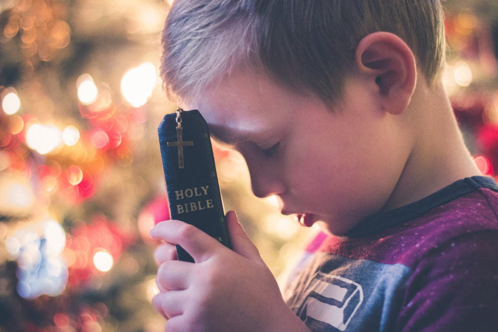 Little boy holding a bible to his forehead