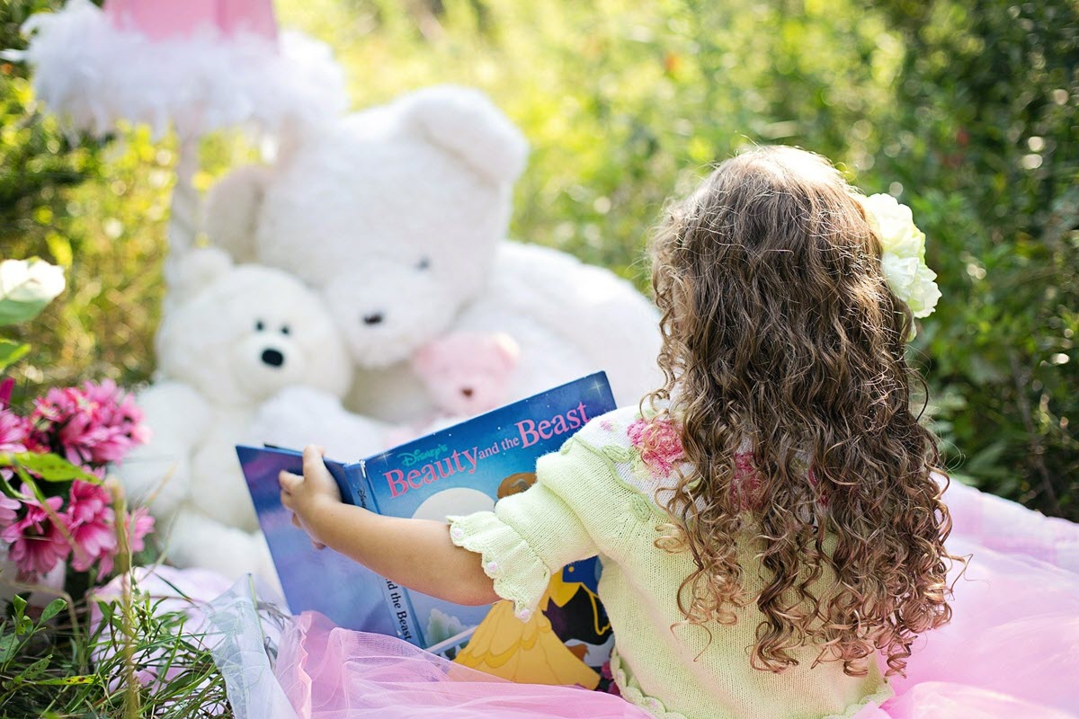 Preschooler girl reading Beauty and the Beast book to her teddy bears