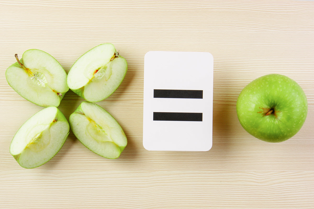 Showing fractions with a green apple cut into fourths