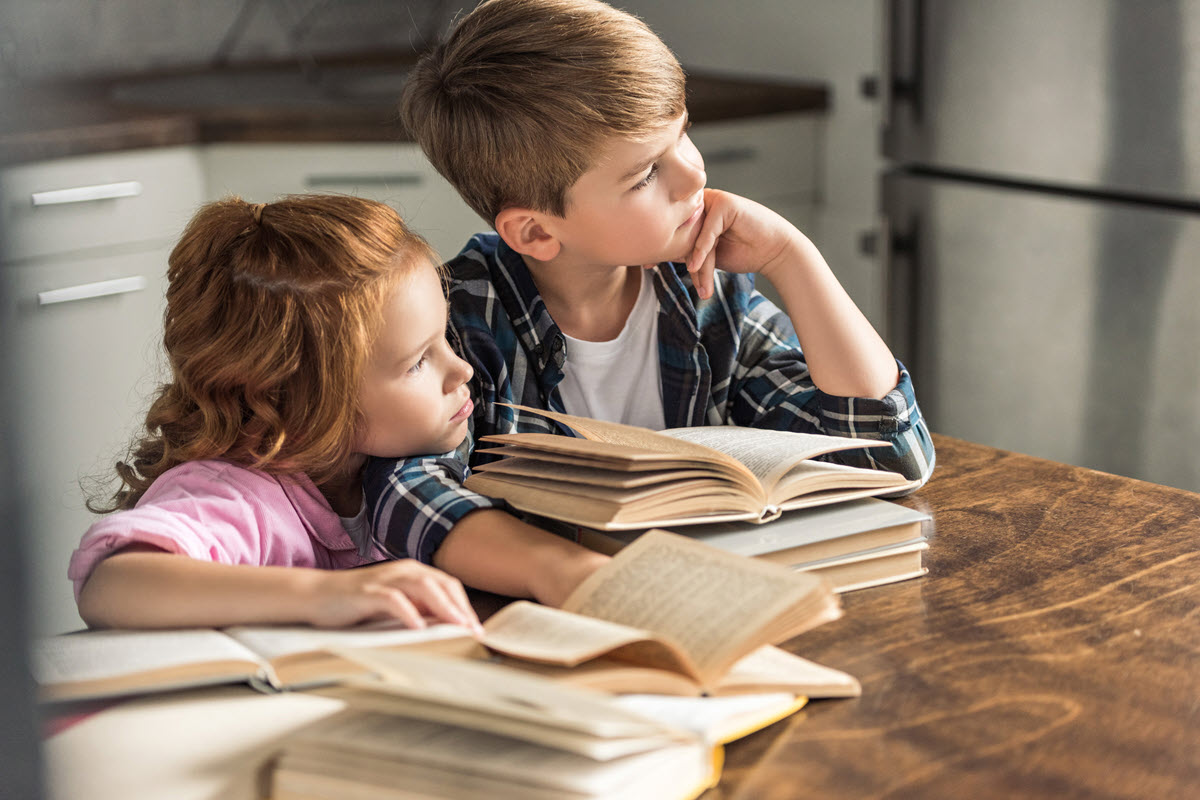 Two kids with piles of books in front of them that need organizing
