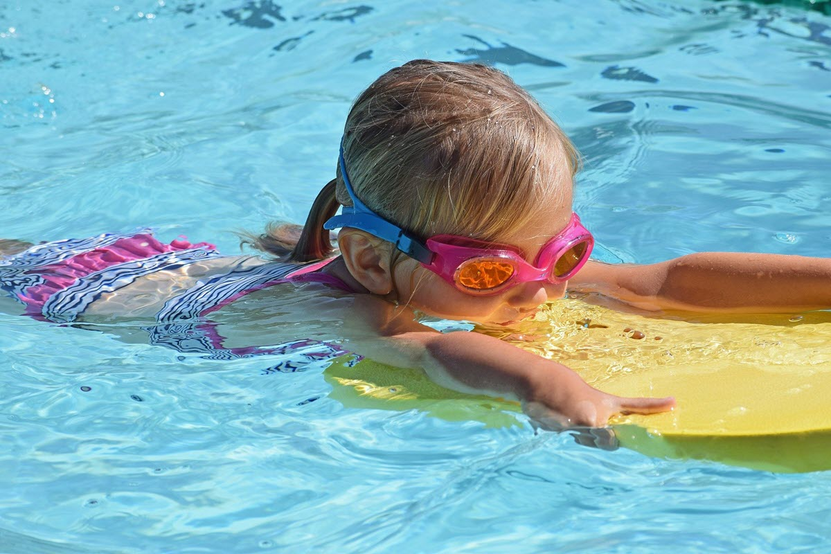Young girl swimming in a pool with goggles and a yellow kick board