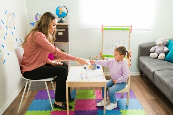Woman teaching addition and subtraction to a preschool child using flashcards