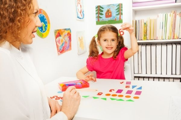 Woman teaching child regrouping by drawing colorful shapes and numbers